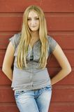At the Barn. Blond teen standing in front of a red barn wall royalty free stock photo