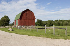 Barn. A barn with a fence under a blue sky on a large green meadow. Dirt road along the green meadow Royalty Free Stock Image