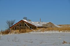 Barn Abandoned, Forgotten, and Snowed Upon. Old crumbling rickety barn covered by snow no longer serves any useful purpose but  provide memories Royalty Free Stock Photography