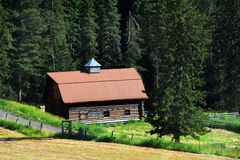 Barn in Absaroka Foothills. Old log barn has been restored by adding a new tin roof.  Barn sits in the foothills of the Absaroka Mountains in Montana.  Country Royalty Free Stock Photo