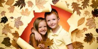 Barn annonserar din produkt och tjänst Gullig pojke och flicka i hösten som spelar med sidor på höstsidor fotografering för bildbyråer