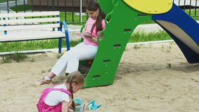 Barn använder en datorminnestavla, går på lekplatsen stock video