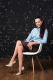 Barn attraktiv lyckad affärskvinna som sitter på en stol Arkivbild
