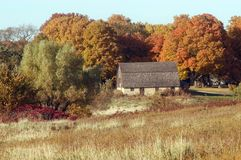 Barn And Autumn Colors. A barn sits quietly tucked in among trees showing their autumn colors Royalty Free Stock Photography