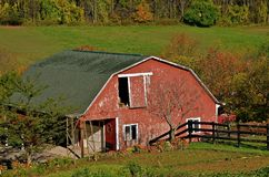Barn in Autumn Colors. The autumn colors are appearing on the red barn with a basketball hoop on the wall Stock Photo