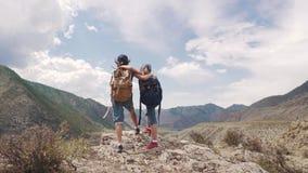 Barn av handelsresanden omfamnar och tycker om den härliga sikten av bergen två små flickor med ryggsäckar på a arkivfilmer