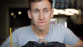Barn av mannen i svarta handskar som äter en hamburgare i ett kafé arkivfilmer