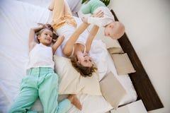 Barn av tre systrar i morgonen på sängen i sovrummet arkivbilder