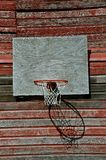 Barn Basketball. An old basketball, rim, and net hang from the backboard against the weathered red siding of a barn Royalty Free Stock Photography