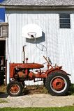 Barn basketball with tractor. A basketball rim missing it's net i attached to a granary with a red tractor parked on the court Royalty Free Stock Image