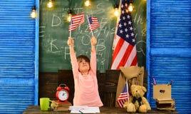 Barn beh?ver den privata lagledaren att h?lla upp med gruppen USA-flagga och en svart tavla Tutor ska kräva barnet att lära royaltyfri bild