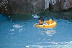 Barn behandla som ett barn i simbassängen Arkivfoto