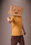 Barn bemannar att göra en gest med en kartong på hans huvud med smiley Fotografering för Bildbyråer