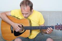 Barn bemannar att leka en gitarr Arkivfoto