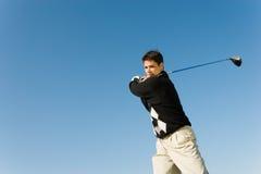 Barn bemannar den svängande golfklubben Royaltyfri Foto