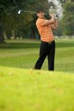 Barn bemannar den svängande golfklubben Arkivbilder