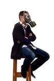 Man med gasmasksammanträde på stol Royaltyfri Fotografi