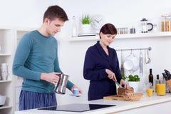 Barn bemannar och den lyckliga kvinnan som förbereder frukosten i deras kök Royaltyfri Fotografi
