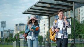Barn bemannar och flickan St? p? h?llplatsen Sun ?r gl?nsande Manen som anv?nder hans mobil, ringer Vänta på hans spårvagn Stad arkivfilmer