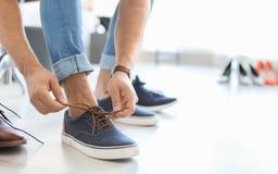 Barn bemannar pröva skor på arkivbilder