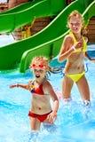 Barn bevattnar på glidbanan på aquapark. Royaltyfri Fotografi