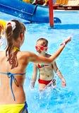 Barn bevattnar på glidbanan på aquapark. Royaltyfri Bild
