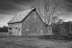 Barn in black and white in a rural area. A decaying barn in a rural in a rural area in black and white royalty free stock photography
