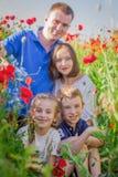 Barn bland vallmofält med föräldrar ut ur fokus Arkivbild