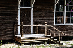 Barn building entry. A closed wooden barn door at the top of a set of stairs on old weathered building Royalty Free Stock Image