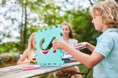 Barn bygger ett hus ut ur pusselstycken fotografering för bildbyråer