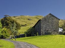 Barn conversion in countryside. Scenic view of stone barn conversion in countryside with hills in background, Cumbria, England royalty free stock photography