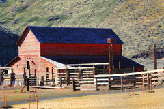 Barn and Corrals. A large red working country barn with corrals sitting at the base of some steep grassy sagebrush hills Royalty Free Stock Images