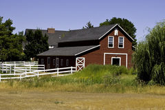Barn in countryside. Exterior of large wooden red barn in countryside; field in foreground Royalty Free Stock Photo