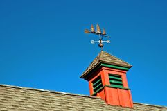 Barn Cupola. A view of a red cupola and weather vane on top of a barn on a sunny, cloudless summer day stock photo