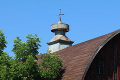 Barn Cupola. The old barn& x27;s partly rusted cupola shows against the bright blue sky with green trees up front royalty free stock images