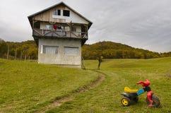 Barn cyklar nära oavslutat hus arkivfoto