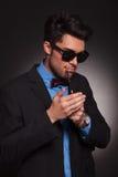 Barn danar manen som tänder hans cigarett Fotografering för Bildbyråer