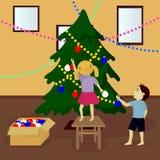 Barn dekorerar julgranen Arkivfoton