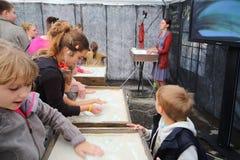Barn deltar mästarklass av sandanimeringen Royaltyfria Foton