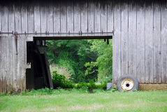 Barn door. Old barn with barn door open and old tire lying next to it Stock Photos