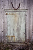 Barn door. Old wood barn door with faded blue-green paint and rusty hinges. The picture was taken during spring season Stock Photo