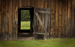 Barn door open on green landscape Royalty Free Stock Photo