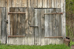 Barn doors. The doors of an old barn with rusty hindges and old milk cans in front show fine detail and beautiful colours Royalty Free Stock Photo