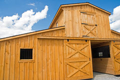 Barn doors and windows. A view of a new wooden farm barn with sliding doors and a second story Royalty Free Stock Image