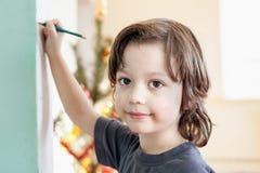Barn drar i hemmet, pojken som studerar teckningen på skolan Royaltyfria Foton