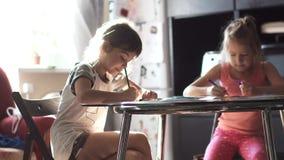 Barn drar med hemmastatt sammanträde för blyertspennor på en tabell systern för två små flickor drar tillsammans i köket lager videofilmer