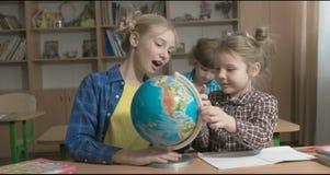 Barn eller två lyckliga flickor som lär och gör läxa i skolaklassrum arkivfilmer