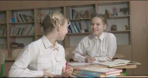 Barn eller två lyckliga flickor som lär och gör läxa i skolaklassrum stock video