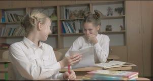 Barn eller två lyckliga flickor som lär och gör läxa i skolaklassrum lager videofilmer