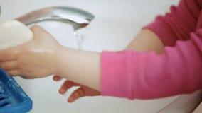 Barn, en flicka eller en pojke, washes hans händer med tvål i en vit vask lager videofilmer